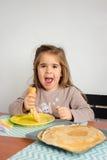 吃堆薄煎饼的年轻疯狂的女孩 免版税库存图片