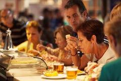 吃塔帕纤维布的游人著名圣米格尔火山市场,马德里 免版税图库摄影