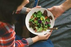 吃夏天沙拉菜的妇女开花金莲花紫罗兰 库存图片