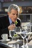 吃外部露台沙拉坐的诉讼表的生意人 免版税库存照片