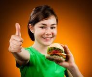 吃大三明治的女孩显示好的符号 免版税库存图片
