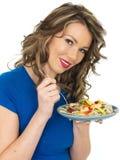 吃大虾和面条沙拉的健康少妇 免版税库存图片