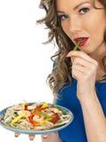 吃大虾和面条沙拉的年轻健康妇女 图库摄影