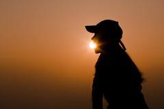 吃太阳剪影的愉快的女孩 免版税图库摄影