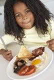 吃女孩不健康的年轻人的早餐 库存照片