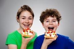 吃女孩奶蛋烘饼的男孩 免版税图库摄影