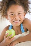 吃女孩客厅年轻人的苹果 免版税图库摄影