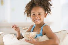 吃女孩客厅微笑的年轻人的谷物 免版税库存照片