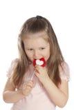 吃女孩小的棒棒糖的糖果 免版税库存图片