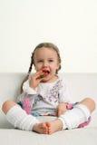 吃女孩少许草莓 库存照片