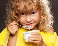 吃女孩少许酸奶 免版税库存照片