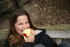 吃女孩年轻人的苹果 库存照片