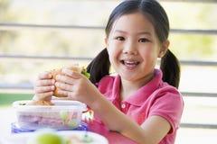吃女孩幼稚园午餐 免版税图库摄影