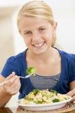 吃女孩户内意大利面食年轻人的brocolli 免版税库存图片