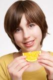 吃女孩桔子片式 免版税库存照片