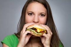 吃女孩汉堡包 免版税库存图片