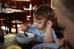 吃女孩的婴孩 库存照片