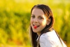 吃女孩的有吸引力的樱桃 免版税库存图片