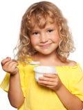 吃女孩的背景查出少许空白酸奶 免版税库存照片