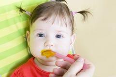 吃女孩的婴孩少许纯汁浓汤蔬菜 免版税图库摄影