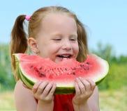 吃女孩西瓜的婴孩 免版税库存图片