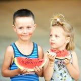 吃女孩西瓜年轻人的男孩 免版税图库摄影