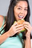 吃女孩讲西班牙语的美国人莴苣的汉堡 免版税库存图片