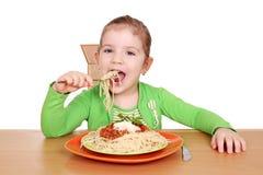 吃女孩饥饿的小的意粉 免版税库存照片