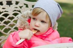 吃奶蛋烘饼用巧克力的孩子在公园 库存图片