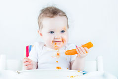 吃她的第一棵红萝卜的甜婴孩 免版税库存照片