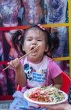 吃她的膳食的亚裔女孩。 免版税库存图片