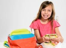 吃她的被包装的午餐的小学女孩 免版税库存图片