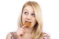 吃妇女年轻人的曲奇饼 免版税库存照片