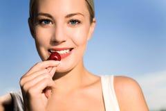 吃妇女年轻人的樱桃 免版税库存照片