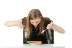 吃妇女年轻人的红萝卜 库存照片