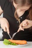 吃妇女年轻人的红萝卜 免版税库存照片