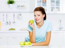 吃妇女年轻人的苹果 免版税库存图片