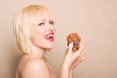 吃妇女的巧克力杯形蛋糕 库存照片