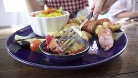 吃妇女的正餐 烤香肠用土豆和菜沙拉 股票视频