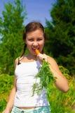 吃妇女的红萝卜 图库摄影