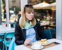 吃妇女年轻人的美丽的早餐 免版税库存图片