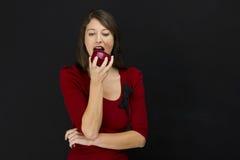 吃妇女年轻人的苹果 免版税库存照片