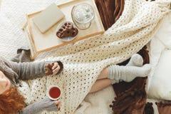 吃姜饼用茶的女孩 免版税库存照片