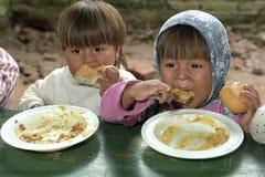 吃孩子在食品配给时 免版税库存照片