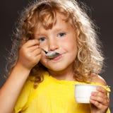 吃孩子酸奶 库存照片