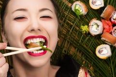 吃寿司卷的美丽的微笑的年轻韩国女孩 免版税库存照片