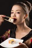 吃寿司卷的迷人的韩国女孩 免版税图库摄影