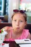 吃寿司的一个小女孩的画象在亚洲餐馆 免版税库存照片