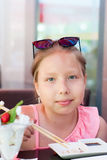 吃寿司的一个小女孩的画象在亚洲餐馆 免版税库存图片
