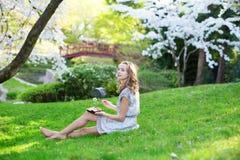 吃寿司的女孩在樱花庭院里 免版税库存图片